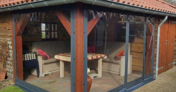 Grijze verandazeilen geplaatst bij blokhut